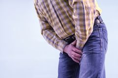 Urolithiasis. Chronic pancreatitis. Stones in the bladder. The man grabbed his groin in a fit of pain.  stock image
