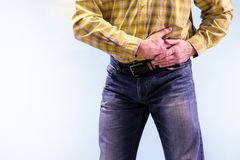 Urolithiasis. Chronic pancreatitis. Stones in the urine. The man grabbed his groin in a fit of pain royalty free stock photos