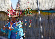 UROS浮动海岛,普诺,秘鲁 2013年5月31日:佩带传统布料的未认出的当地妇女,卖纪念品 免版税库存图片