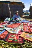 UROS浮动海岛,普诺,秘鲁 2013年5月31日:佩带传统布料的未认出的当地妇女,卖纪念品 库存图片