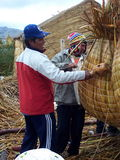 UROS ISLANDS, LAKE TITICACA, PERU - January 3, 2007: Uros men build a totora reed boat. Uros men build a totora reed boat on a floating island on Lake Titicaca Royalty Free Stock Photography