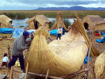 UROS ISLANDS, LAKE TITICACA, PERU - January 3, 2007: Uros men build a totora reed boat. Royalty Free Stock Photography