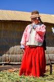 UROS SPŁAWOWE wyspy, PUNO, PERU MAJ 31, 2013: Niezidentyfikowana rodzima kobieta jest ubranym tradycyjnych płótna je trzcinę cukr zdjęcie royalty free