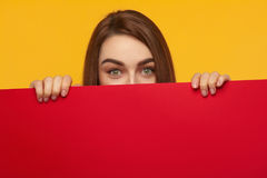 Urprised woman hiding behind sheet of red cardboard. Cheerful young shocked girl standing behind big red colored billboard and looking at camera Royalty Free Stock Images