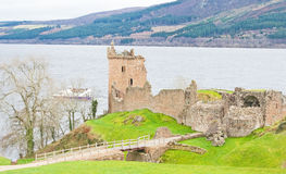 Urquart Castle and boat. Urquhart Castle, Loch Ness and tourists on the boat Jacobite Legend Stock Image