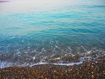 Urquoisezeewater met golven en schuim, overzees kiezelsteenstrand met gekleurde, kleurrijke kiezelstenen Royalty-vrije Stock Afbeelding