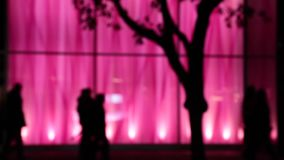 Urrban night people walking bright pink curtain. Pedestrians passing by pink background Vancouver downtown stock footage