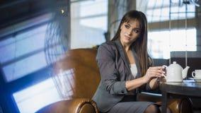 Ursnygg affärskvinna som har arbetsavbrottet, medan sitter i near kopieringsutrymme för kafét för ditt befordrings- innehåll Dröm Royaltyfri Foto