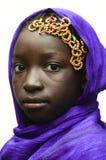 Ursnygg afrikansk skolflicka som utomhus poserar med en Violet Head S royaltyfri bild