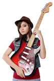 Ursnygg asiatisk flicka som rymmer hennes gitarr, på vit bakgrund Royaltyfri Foto