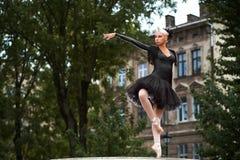 Ursnygg ballerina i svart dräktdans i stadsgatorna fotografering för bildbyråer