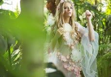 Ursnygg blond nymf som går i skogen royaltyfri foto