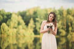 Ursnygg brud i den hållande buketten för elegant klänning som poserar nära skog och sjön royaltyfri foto