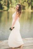 Ursnygg brud i den hållande buketten för elegant klänning som poserar nära skog och sjön Arkivbild