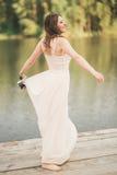 Ursnygg brud i den hållande buketten för elegant klänning som poserar nära skog och sjön Royaltyfri Fotografi
