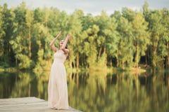 Ursnygg brud i den hållande buketten för elegant klänning som poserar nära skog och sjön Arkivbilder