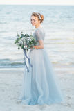 Ursnygg brud med bröllopbuketten vid havet Arkivfoto
