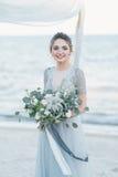 Ursnygg brud med bröllopbuketten vid havet Arkivbild