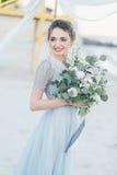 Ursnygg brud med bröllopbuketten vid havet Royaltyfri Bild