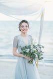 Ursnygg brud med bröllopbuketten vid havet Arkivfoton