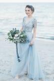Ursnygg brud med bröllopbuketten vid havet Royaltyfria Bilder