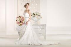 Ursnygg brud med den vita klänningen med blommabuketten Royaltyfria Bilder