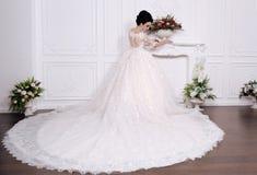 Ursnygg brud med mörkt hår i luxuious bröllopsklänning arkivbilder