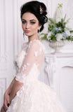 Ursnygg brud med mörkt hår i luxuious bröllopsklänning royaltyfria bilder