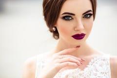 Ursnygg brud med modemakeup och frisyr i en lyxig bröllopsklänning