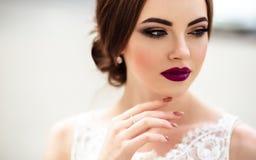 Ursnygg brud med modemakeup och frisyr i en lyxig bröllopsklänning Arkivbilder
