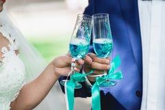 Ursnygg brud och brudgum som rostar med champagne som gifta sig morgon händer som rymmer stilfulla exponeringsglas av blått vin Arkivbilder