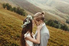 Ursnygg brud och stilfull brudgum som kramar på det soliga landskapet, bo Royaltyfria Foton