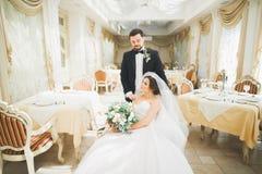 Ursnygg brudgum som kramar försiktigt den stilfulla bruden Sinnligt ögonblick av lyxiga brölloppar royaltyfri fotografi