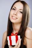 Ursnygg brunett med gåva Arkivbild