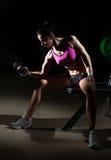 Ursnygg brunett som lyfter något vikter och arbete på hennes biceps i en idrottshall Konditionkvinna som gör genomkörare Sportig  Arkivfoton