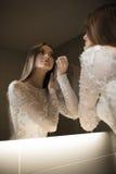 Ursnygg brunettkvinna i hennes bröllopsklänning som ser sig i spegeln som gör makeup fotografering för bildbyråer