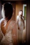 Ursnygg brunettkvinna med långt hår och blåa ögon som ser sig i spegeln Royaltyfri Bild