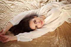Ursnygg brunettkvinna som kopplar av att ligga i damunderkläder på säng Fotografering för Bildbyråer