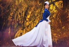 Ursnygg brunettskönhet i en gammalmodig klänning Royaltyfri Fotografi