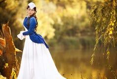 Ursnygg brunettskönhet i en gammalmodig klänning Arkivfoton