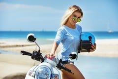 Ursnygg dam med hjälmen och oldstyle sparkcykel på den tropiska stranden royaltyfri bild
