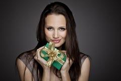 Ursnygg flicka med gåvan på mörk bakgrund Arkivbild