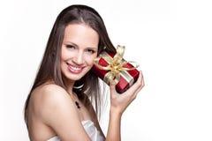 Ursnygg flicka med gåvan på vit bakgrund Arkivbild