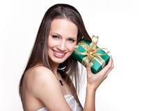 Ursnygg flicka med gåvan på vit bakgrund Royaltyfria Bilder