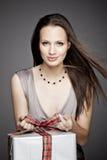 Ursnygg flicka som rymmer en gåva i henne händer Arkivfoto