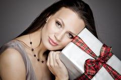 Ursnygg flicka som rymmer en gåva i henne händer Arkivfoton