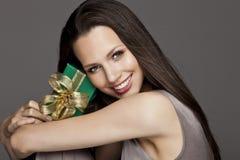 Ursnygg flicka som rymmer en gåva i henne händer Royaltyfria Foton