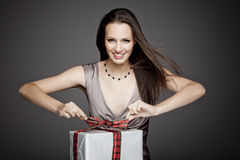 Ursnygg flicka som rymmer en gåva i henne händer Royaltyfria Bilder