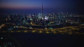 Ursnygg flyg- surrcityscapepanorama av futuristiska moderna torn i det nattljusDubai centret arkivfilmer