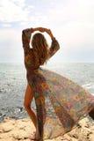 Ursnygg kvinna med blont hår i den eleganta baddräkten som poserar på stranden royaltyfria bilder
